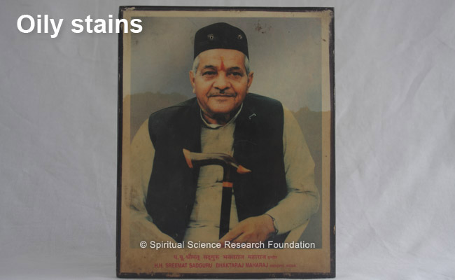 Oily like stains permeating through a laminated picture of His Holiness Bhaktaraj Maharaj